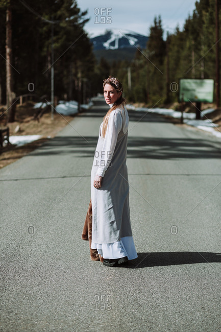 Full length serene thoughtful female in white loose dress standing with coat in hand