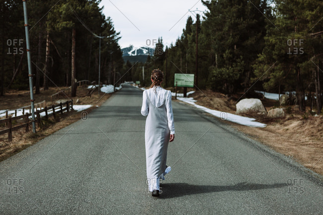 Back view young female wearing casual maxi dress strolling along empty asphalt road between evergreen forest in early spring