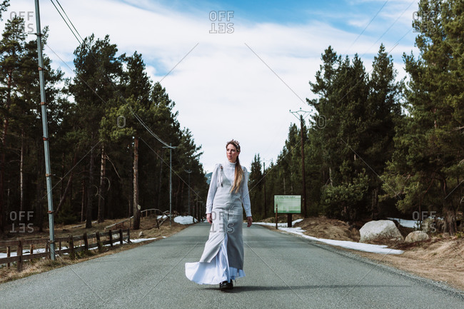 Full body serene young female wearing casual maxi dress strolling along empty asphalt road between evergreen forest in early spring