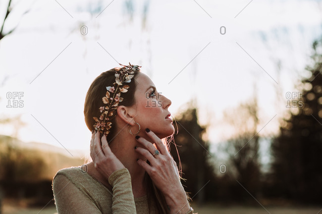Sensitive young female wearing stylish copper wreath touching neck tenderly and looking up while standing in peaceful summer park