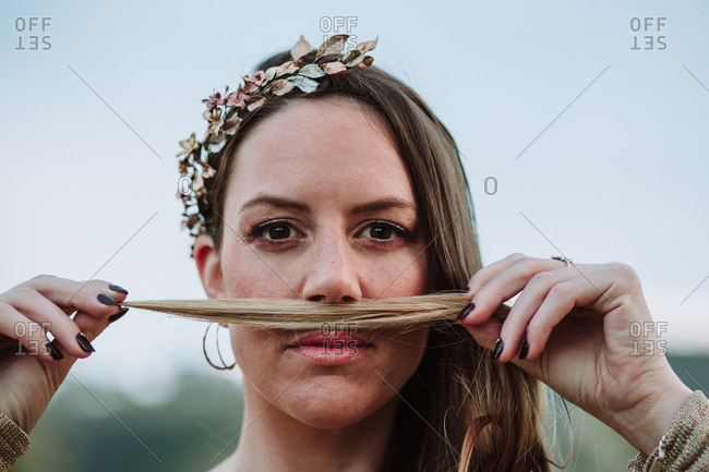 Calm female wearing copper wreath holding strand of hair under nose and looking at camera while standing against blurred nature background