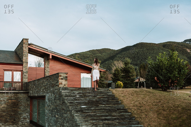 Full length faceless slim female wearing stylish outfit strolling on modern cottage stairs located in hilly lush countryside