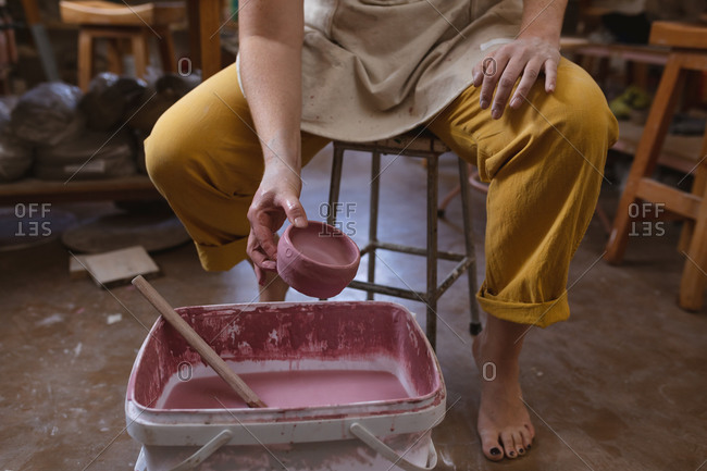 Caucasian female potter in face mask working in pottery studio.