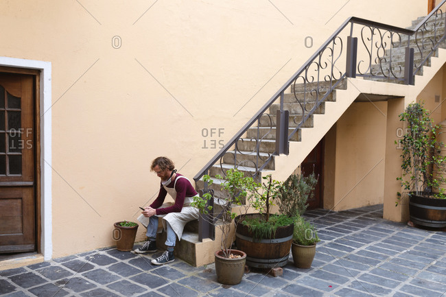 Caucasian male potter sitting on stairs outside pottery studio.