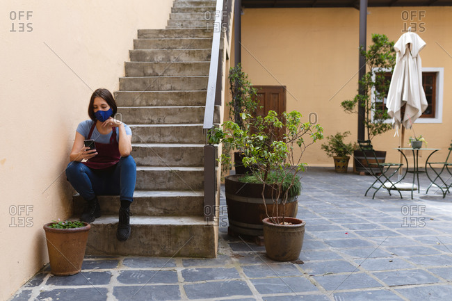 Caucasian female potter sitting on stairs outside pottery studio.