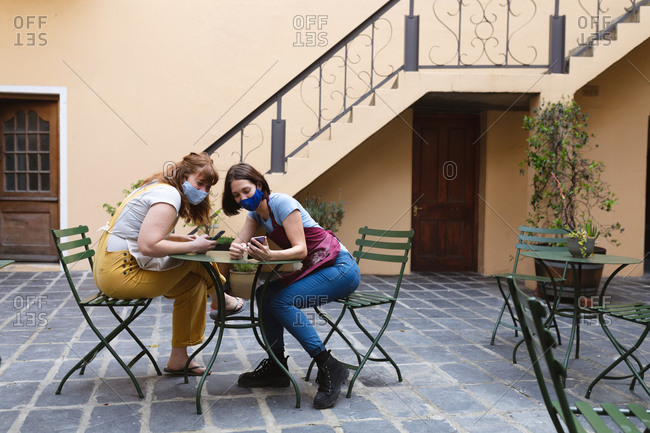 Two caucasian female potter sitting by table outside pottery studio.