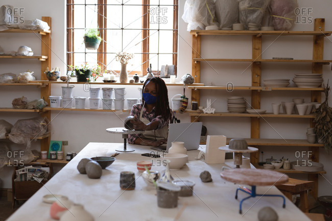 Mixed race female potter in face mask working in pottery studio.