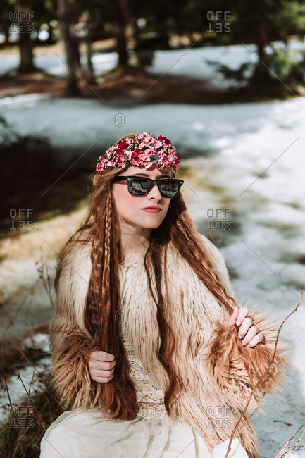 Attractive young long haired female in fur jacket and sunglasses with floral wreath on head