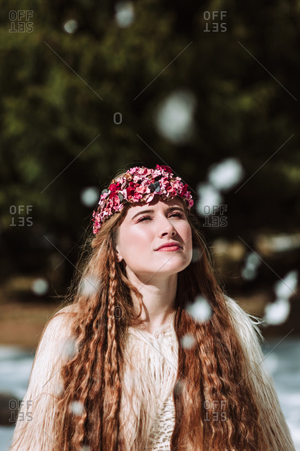 Young blonde female in boho style wedding dress and fur jacket with floral wreath on head standing on snowy meadow against forest