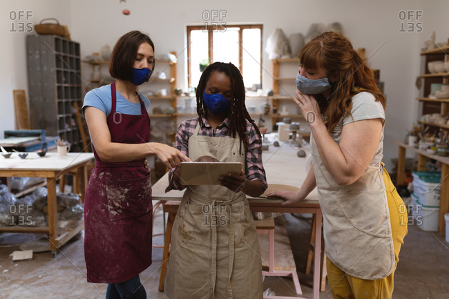 Two caucasian and one mixed race female potters in face mask working in pottery studio.