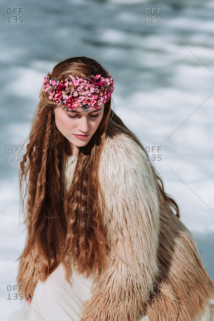 Young blonde female in boho style wedding dress and fur jacket with floral wreath on head