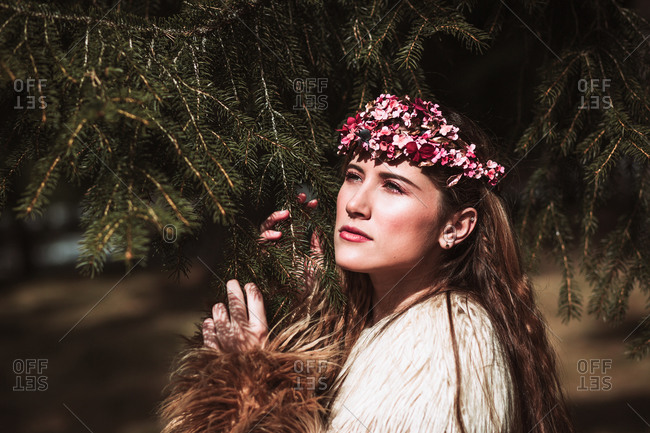 Charming romantic young long haired female with pink floral wreath standing near spruce branches and looking away