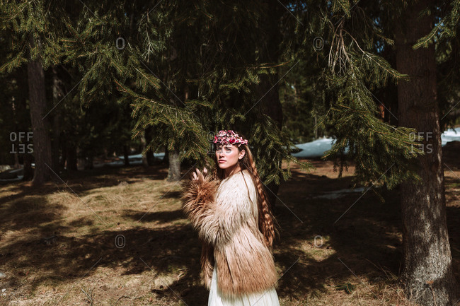Charming romantic young long haired female with pink floral wreath standing hugging tree spruce branches and looking away