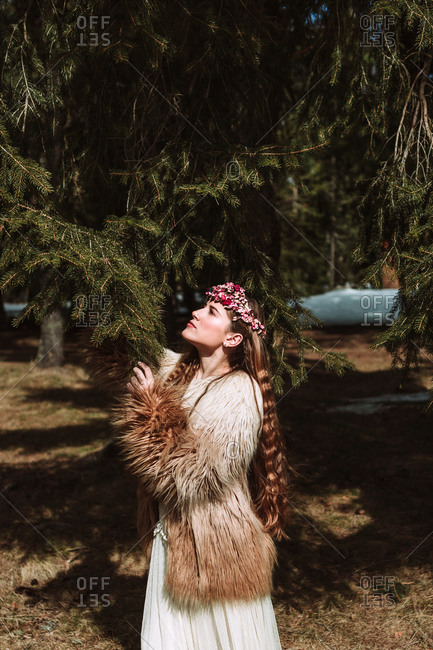 Charming romantic young long haired female with pink floral wreath standing hugging tree spruce branches and looking up