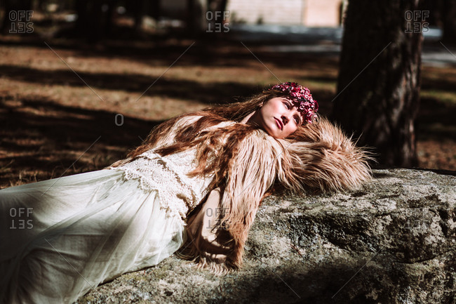 Charming dreamy young female model in long white dress and fur jacket with wreath on head lying on stone on forest meadow