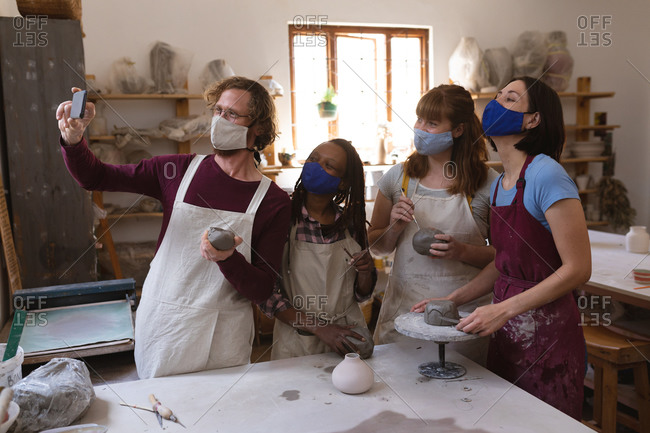 Multi-ethnic group of potters in face masks working in pottery studio.