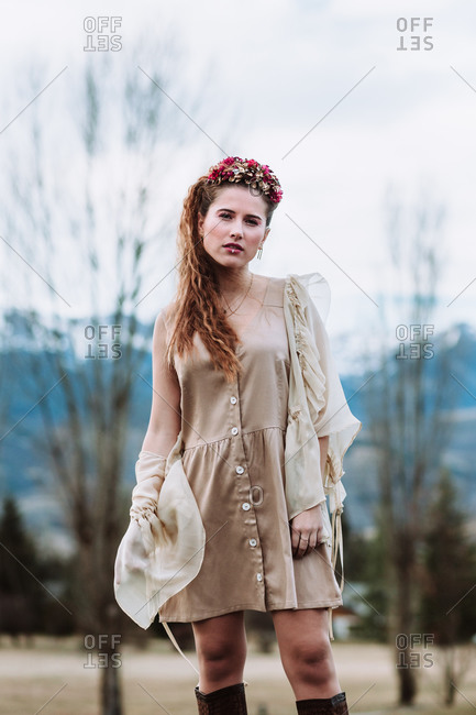 Confident young long haired female in stylish dress and warm jacket with floral wreath on head
