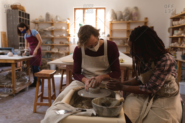 Caucasian male and mixed race female potters in face masks working in pottery studio.