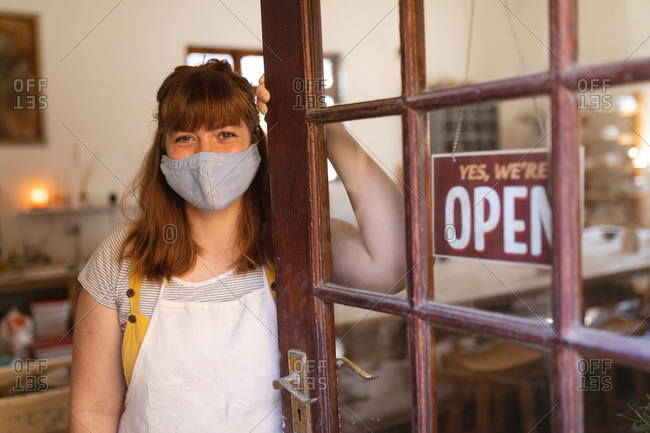 Portrait of caucasian woman wearing face mask at pottery studio.