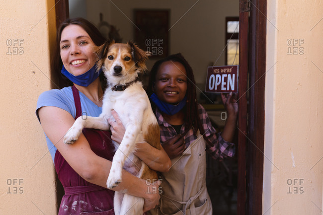Portrait of caucasian and mixed race women at pottery studio, holding a puppy.