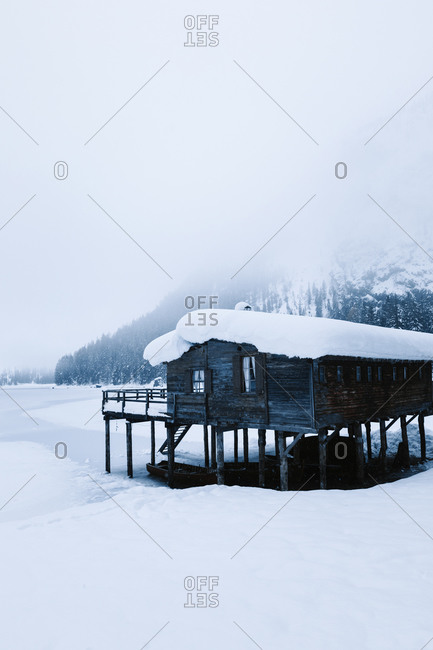 Cold winter landscape with lonely stilt house located near frozen river in snowy mountain valley in dense snowstorm