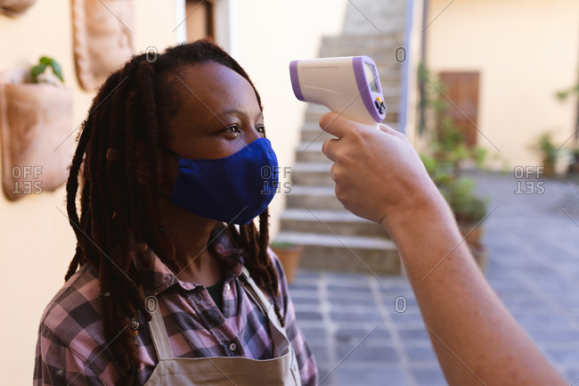 Mixed race female potter in face mask outside of pottery studio.