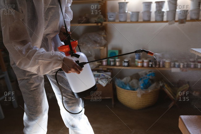 Caucasian male cleaner in protective clothes working in pottery studio. disinfecting the whole place.