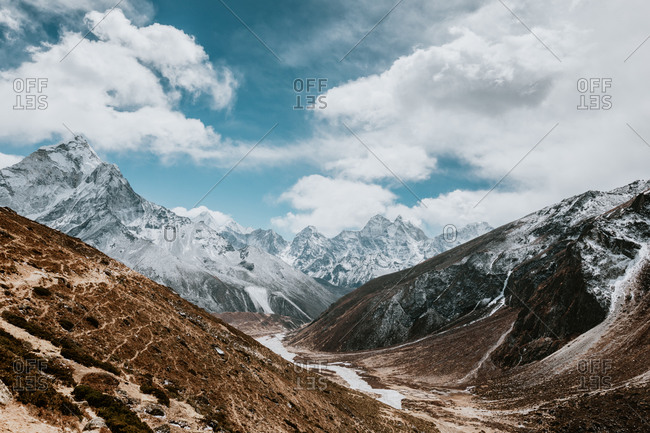 Majestic scenery of desert rough rocky mountainous terrain under blue cloudy sky in sunny day