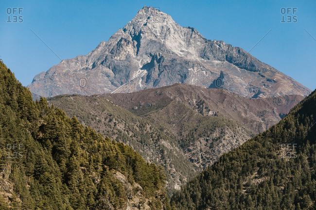 Majestic scenery of desert rough rocky mountainous terrain under blue sky in sunny day