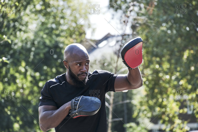 Portrait of muscular male coach with red boxing pad gloves