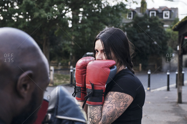 Strong brunette woman boxing outdoors with her personal coach.
