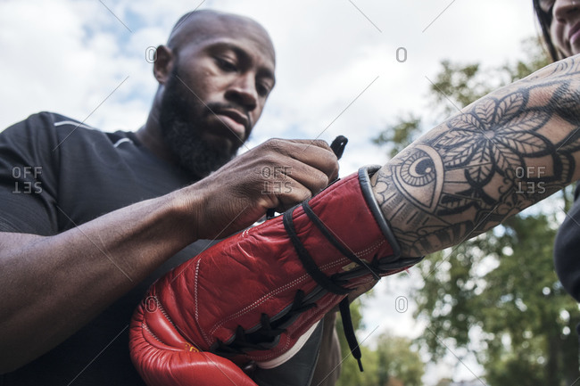 Man coach help woman to tying boxing glove on hand