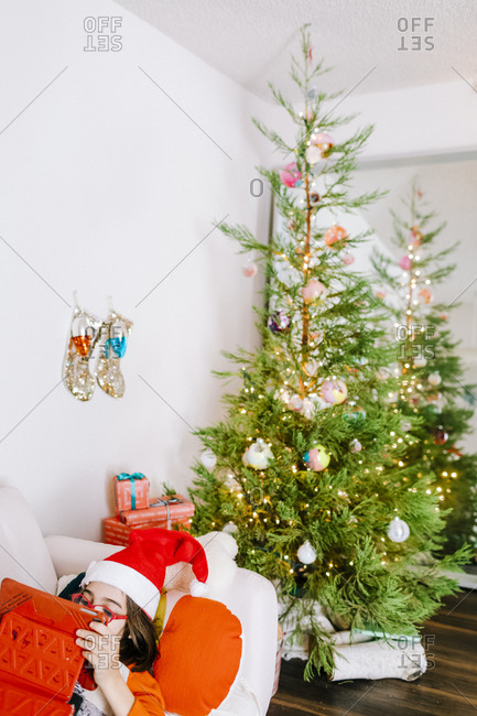 Kid wearing santa hat lying in coach by christmas tree and lights at home