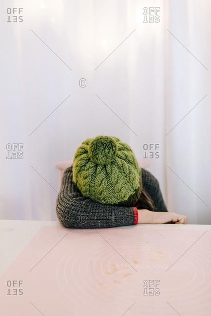 Child wearing green pom hat hiding reading book by pink table