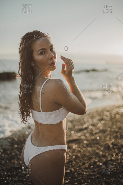 Young sexy girl in sequins and swimsuit in the water on the beach