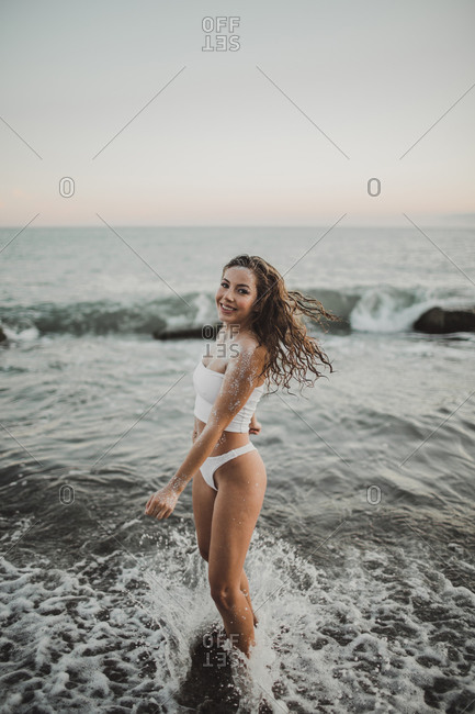 Young sexy girl in sequins and swimsuit stands in the water