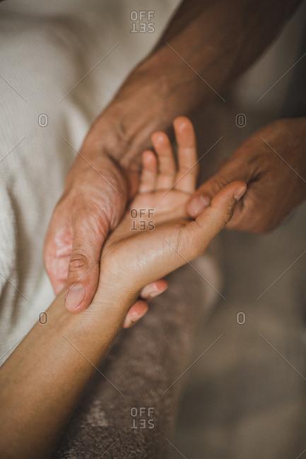 A man massages a woman's hand close up