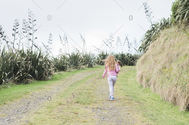 Young girl walking up a grass path holding her doll