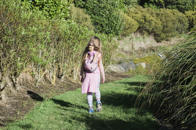Young girl walking in nature reserve with her doll in a backpack