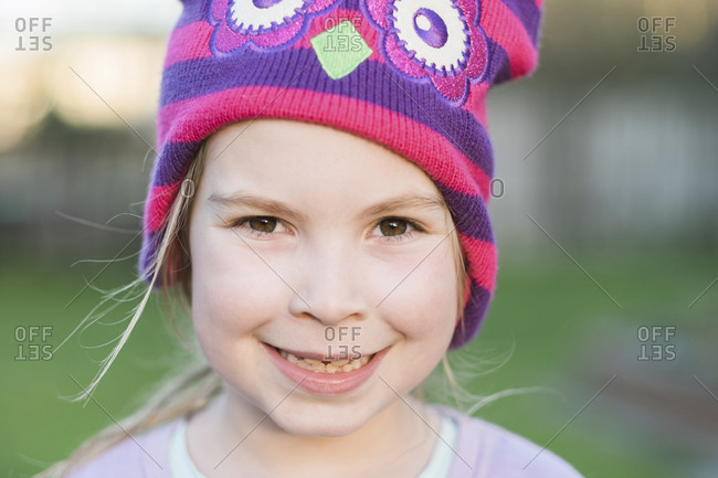 Closeup of a young girl smiling and wearing a colorful hat