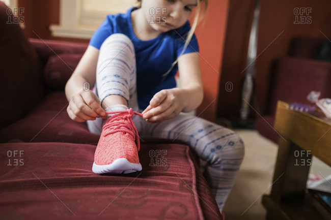 Young girl sitting on sofa and tying a shoe lace on her sneaker