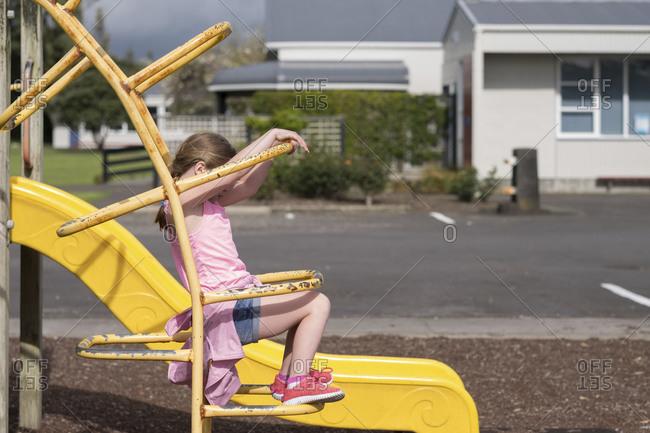 Young girl sitting on yellow playground equipment