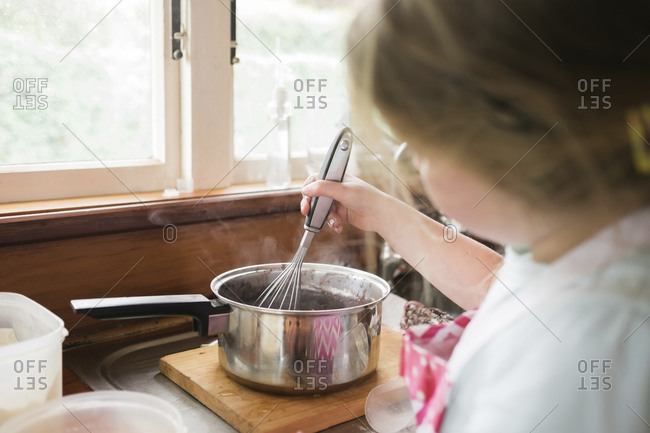 Young girl whisking hot baking mixture in a pot
