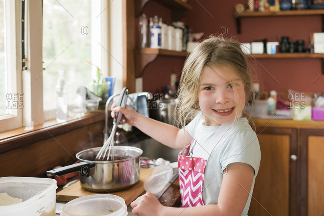 Young girl smiling and mixing hot baking mixture in messy kitchen