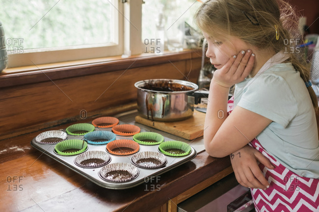 Young looking at mixture in cupcake liners on bench