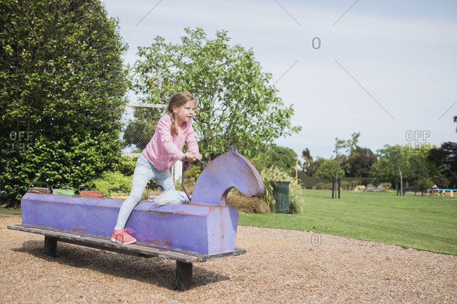 Young girl playing on playground equipment at the park