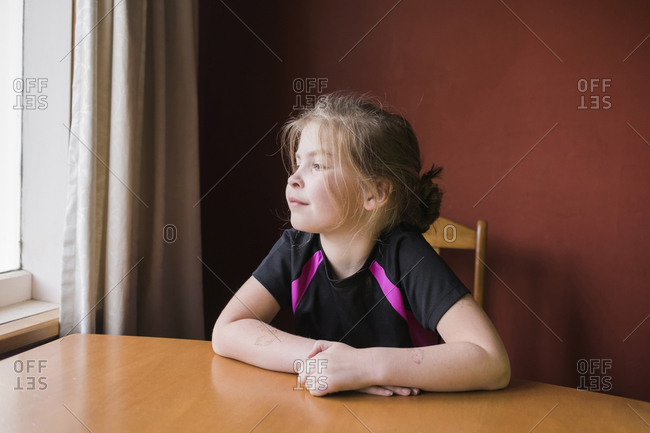 Young girl sitting inside at the dining room table looking outside