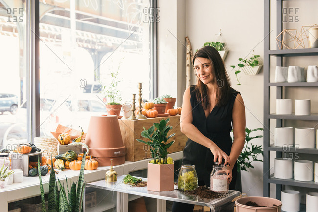 Florist looking to camera in testimonial while building stylish floral