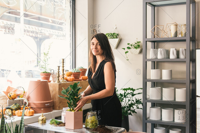 Flower shop business owner working on new potted plants display