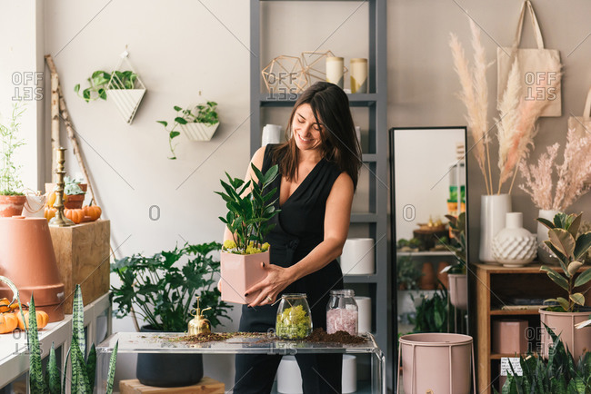 Half body crop of florist smiling and holding new made plant container